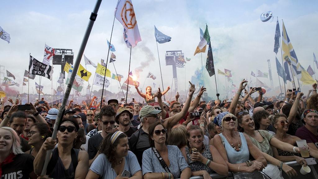 Publik med flaggor på festivalen Glastonbury.