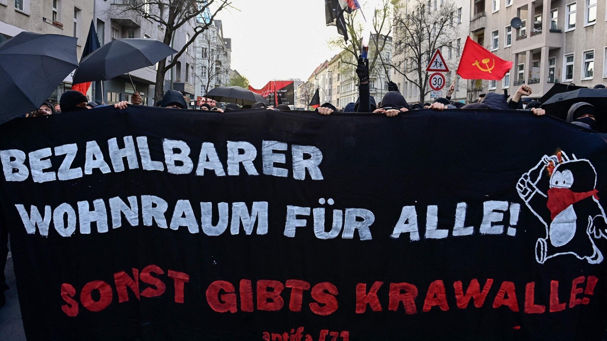 """Protestanter i Berlin håller upp en banderoll där det på tyska står """"Prisvärda bostäder till alla, annars blir det upplopp""""."""