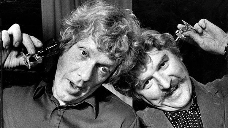 Två personer med glas mot öronen.