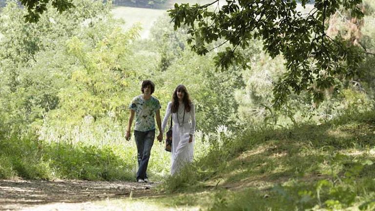"""Ur filmen """"Efter revolutionen"""". Ett par går hand i hand på väg i grönska. Foto: SF"""