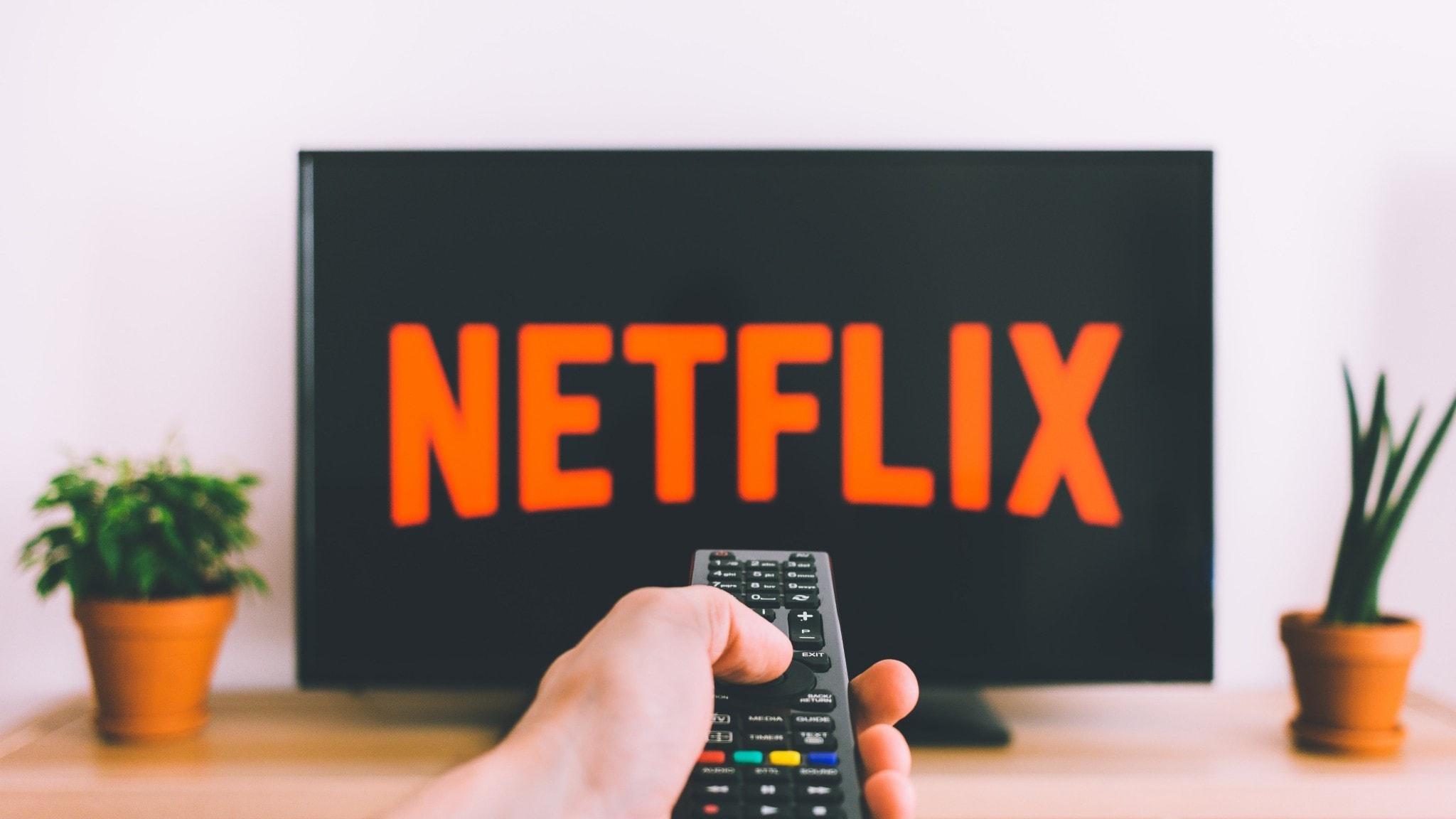 Hand håller fjärrkontroll mot skärm som visar Netflix logga.