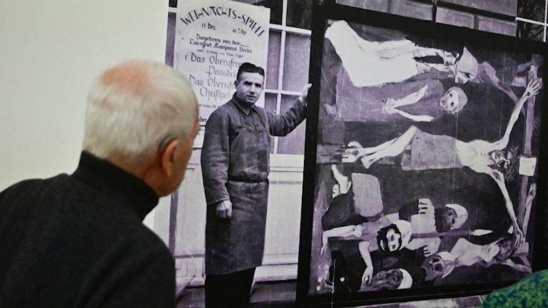 """En man tittar på en bild av Nolde med målningen """"The Life of Christ""""."""