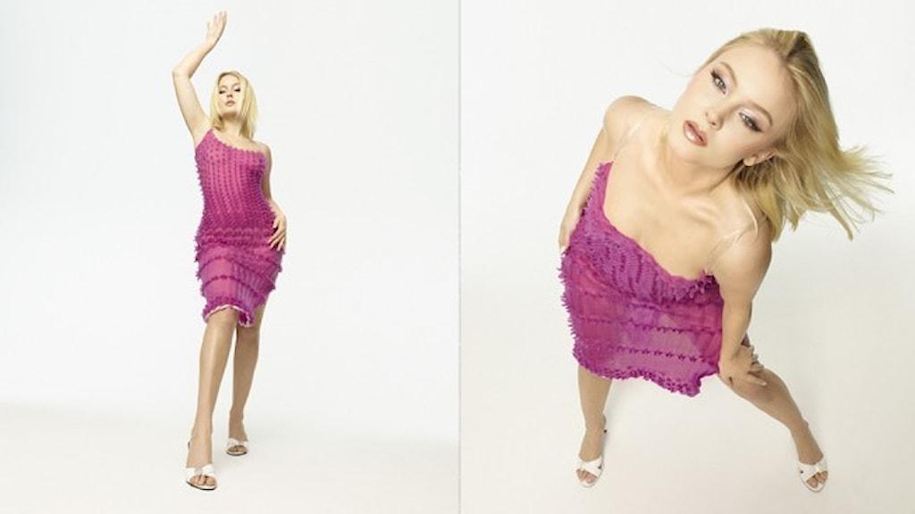 Artisten Zara Larsson klädd i rosa klänning och vita skor.