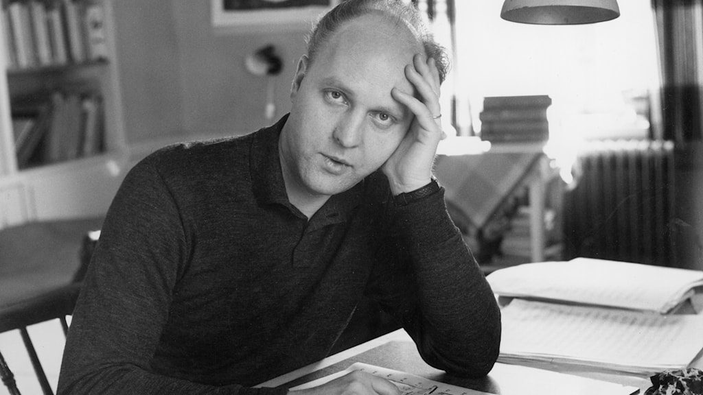Svartvitt porträtt av tonsättaren Ingvar Lidholm vid ett skrivbord.
