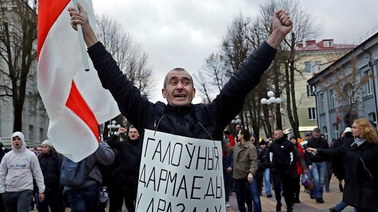 """""""De största parasiterna finns i Drozdy (presidentens bostad)"""" står det på mannens plakat. Fredagens demonstrationer i Maladzyechna, Belarus handlar om den två år gamla lagen om att människor som varit arbetslösa i mer än sex månader måste betala straffavgifter."""