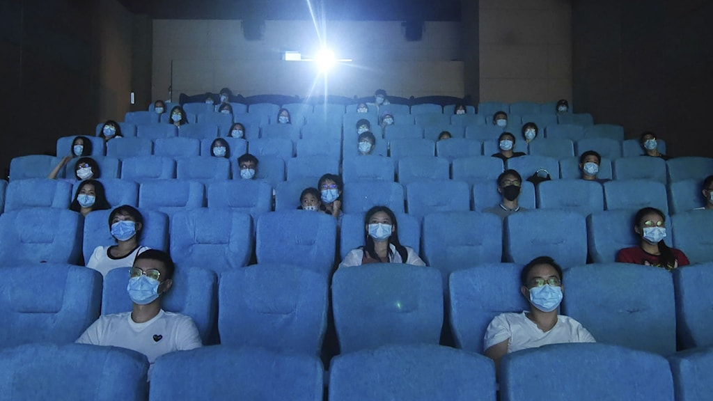 Människor sitter i en gles biosalong med blåsäten, i blått ljus och med blå munskydd.