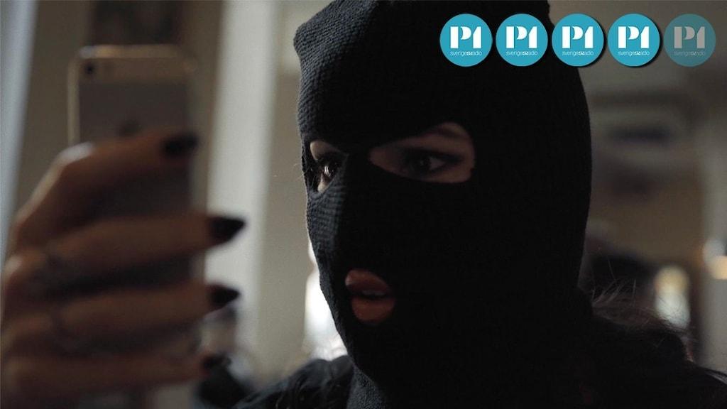 En kvinna i rånarluva håller upp en mobil framför ansiktet.