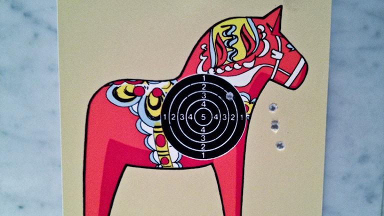 Spridd träffbild på en måltavla i form av en litografi av en dalahäst av konstnären Peter Johansson. Foto: Sara Perers / TT