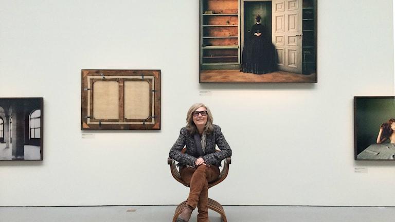 Denise Grünstein framför några av utställningens fotografier. Foto: Hugo Rennéus / Sveriges Radio.