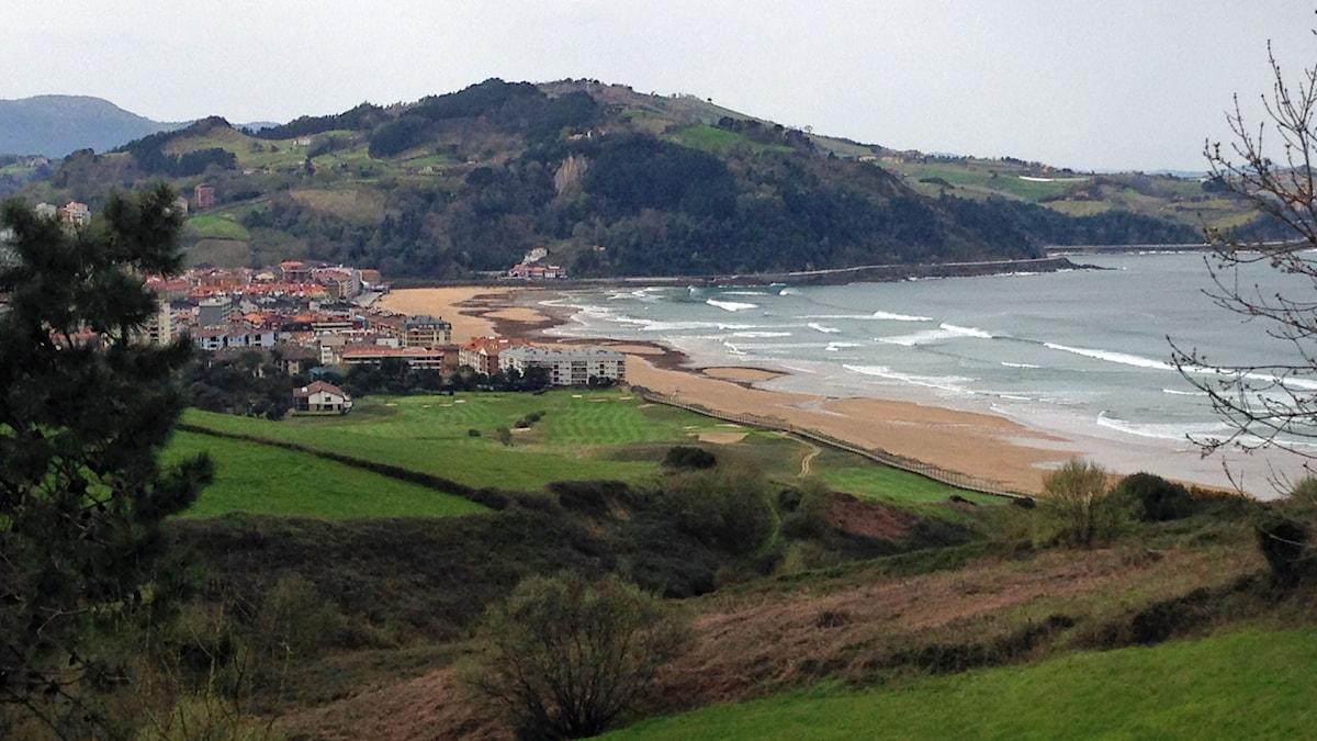 Zarautz från höjden med liten golfbana och vågor för surfare.
