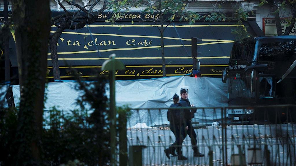 Två poliser framför en presenning som täcker för Bataclan Cafe i Paris