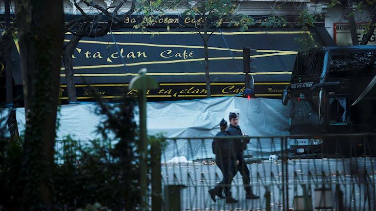 Två poliser framför en presenning som täcker för Bataclan Cafe i Paris på söndagen. Ett 80-tal människor dödades under en konsert på Bataclan under fredagens terrorattack i Paris. Foto: Vilhelm Stokstad / TT