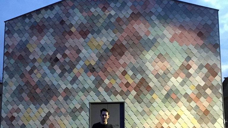 Adam Willis från Assemble framför deras egendesignade fasad av betong-kakel. Foto: Lisa Bergström/SR