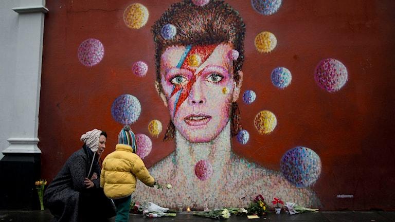 I Brixton, London läggs blommor ner vid en väggmålning föreställande David Bowie. Foto: Matt Dunham/AP/TT.