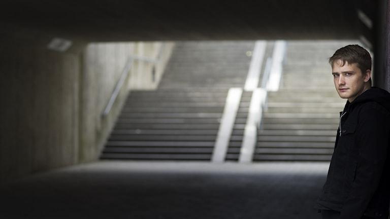Författaren Måns Wadensjö i en tunnel, lutad mot en vägg