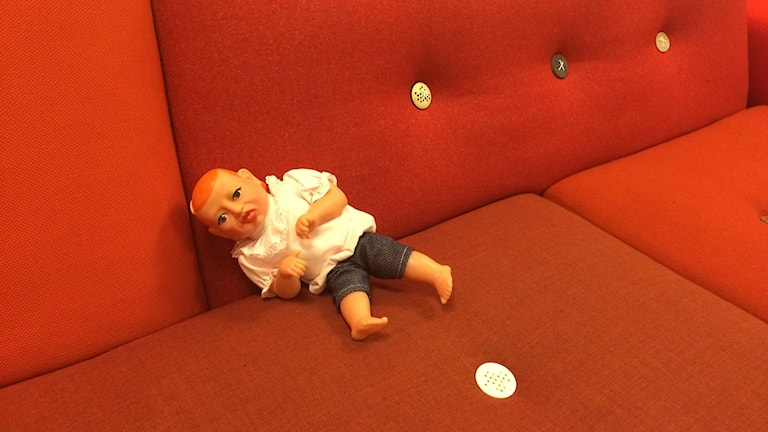 Syntolkning: CP-dockan sitter i en röd soffa på kooperativet GIL:s lokaler i Göteborg. Dockan är av plast och har en vit blus och blåa jeans.