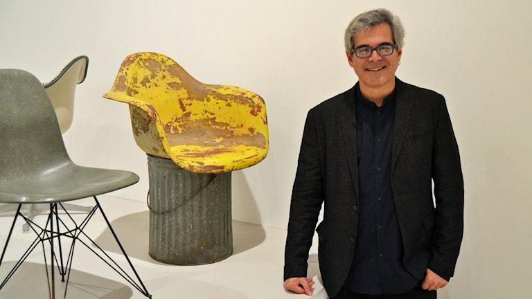 Eames Demetrios vid en humoristisk prototyp till den formgjutna plaststolen. Foto: Peter Öberg, Sveriges Radio.