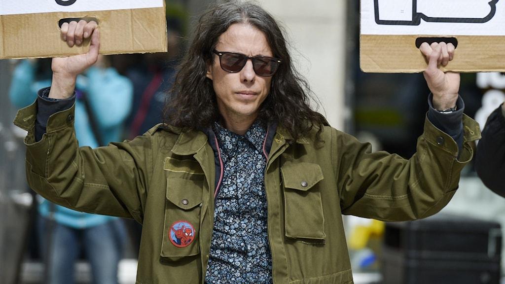 """Konstnären Dan Park, klädd i grön jacka och med långt mörkt hår, håller upp två skyltar: en med en tumme ner märkt """"Islam"""" och en med en tumme upp märkt """"Pegida""""."""