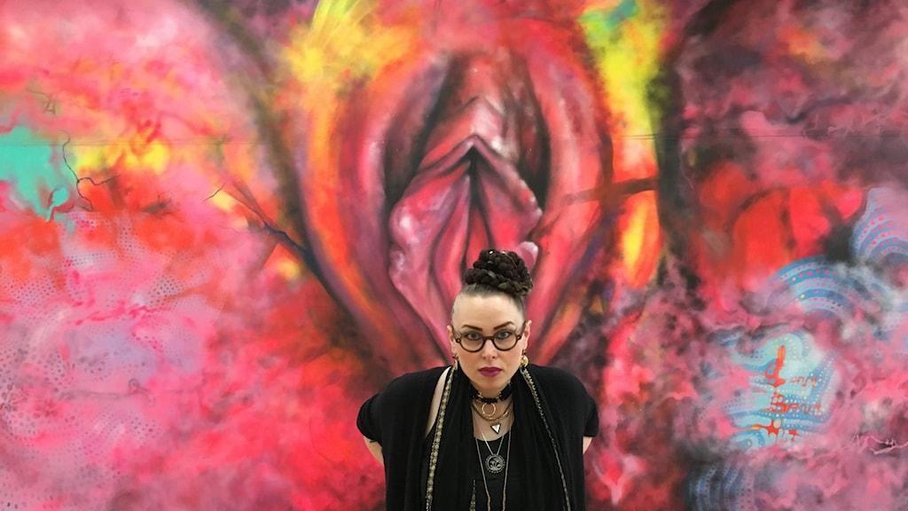 Carolina Falkholt framför sin väggmålning.