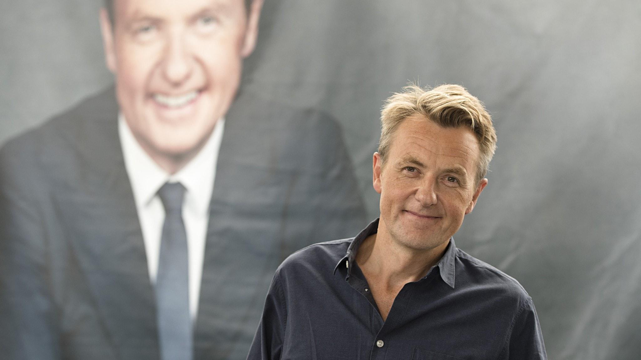 Porträtt av programledaren Fredrik Skavlan framför ett porträtt av sig själv.