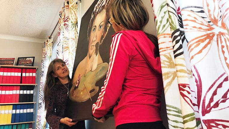 """Ann-Marie Bäckströms konstverk """"Det var en gång"""" hängs upp på väggen hos ett fastighetsföretag i Lycksele."""