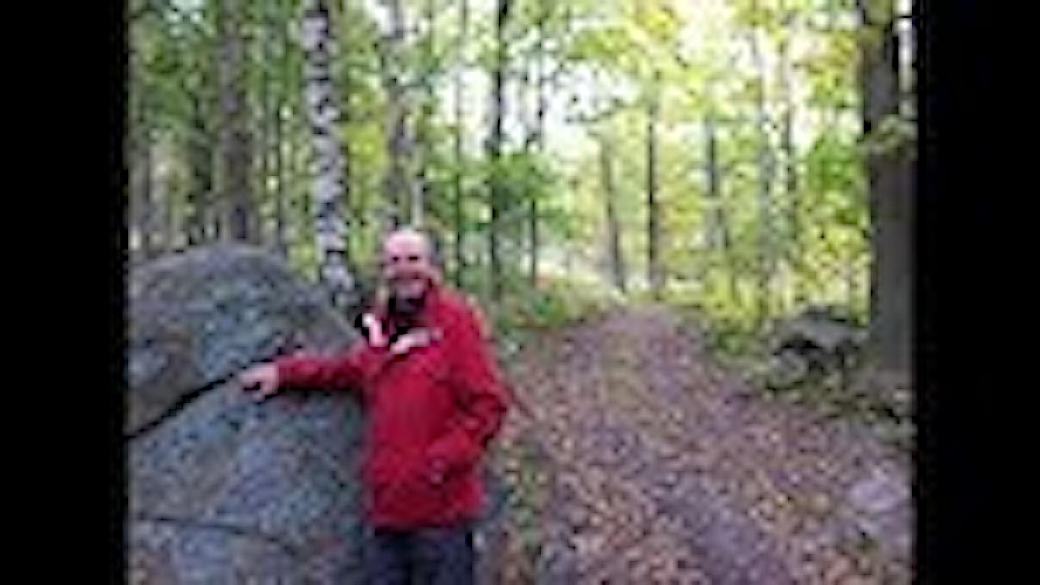 Alf står och lutar sig emot stenen som markerar vägen in på Gröne Grevens stig.