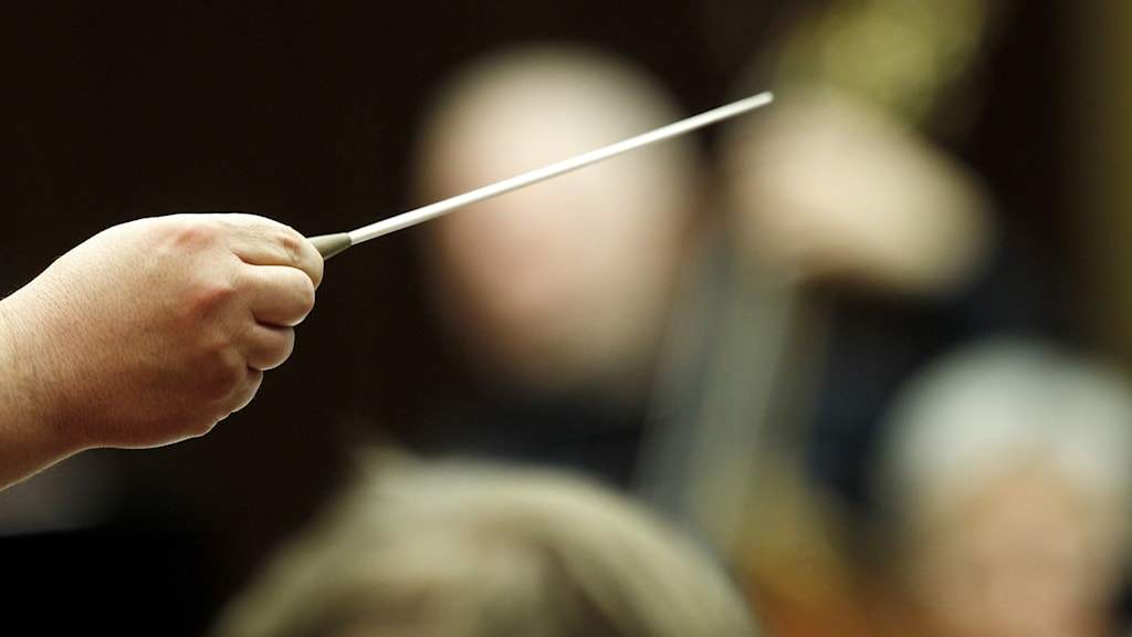 En dirigents hand som håller i en dirigentpinne.
