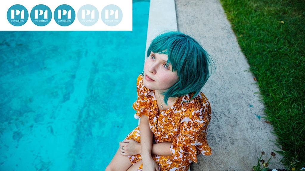 En ung tjej i blå peruk sitter vid en bassängkant.