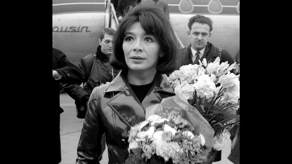 Artisten Juliette Gréco tas emot med blommor på en flygplats.