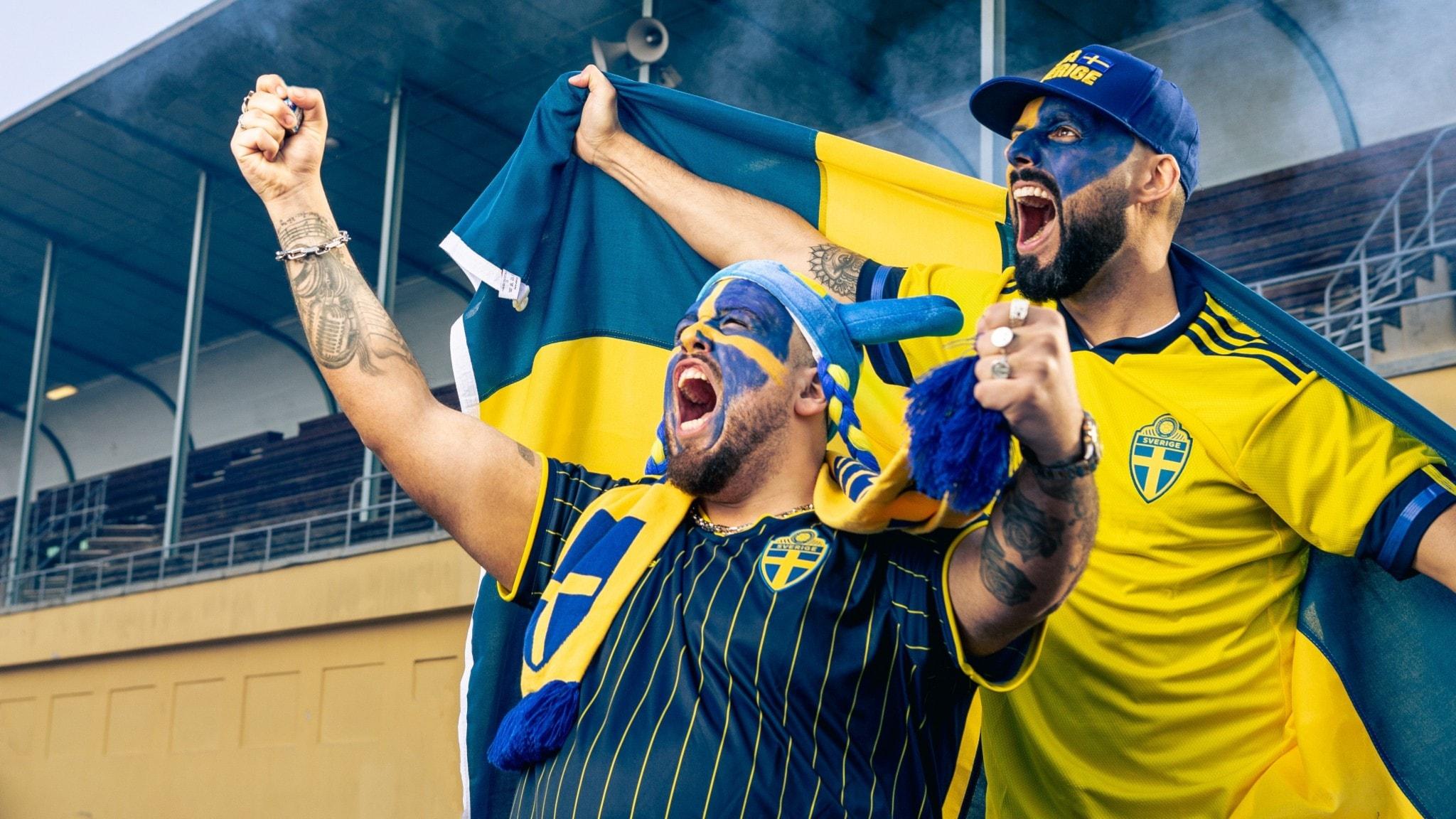 Artisterna Anis Don Demina och SAMI klädda i blågula fotbollskläder, målade i ansiktet och med händerna höjda.
