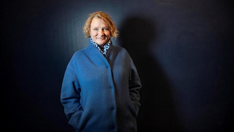 Anna Takanen står i en blå kappa mot wen mörk bakgrund.