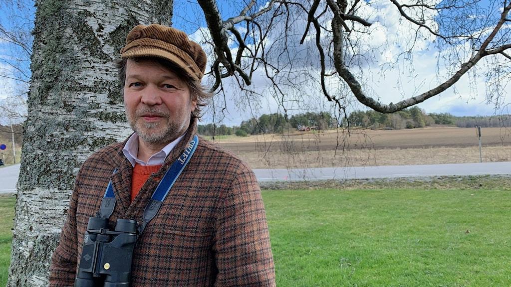 """Författaren Tomas Bannerhed skriver om fåglar i sin nya bok """"En vacker dag"""", han poserar i manchsterkeps och rutig kavaj och med en kikare runt halsen vid en björk vid Lovö kyrka."""