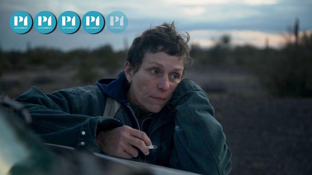 Huvudpersonen Fern i filmen Nomadland står lutad mot sin van med en cigarett i handen.