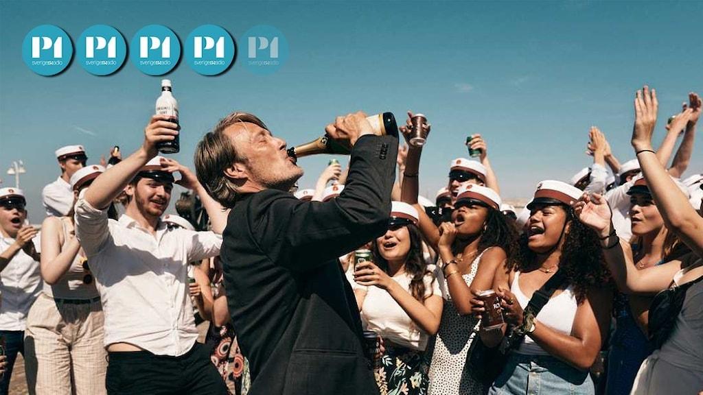 """Skådespelaren Mads Mikkelsen dricker direkt ur en champagneflaska under en studentavslutning, scen ur filmen """"En runda till""""."""