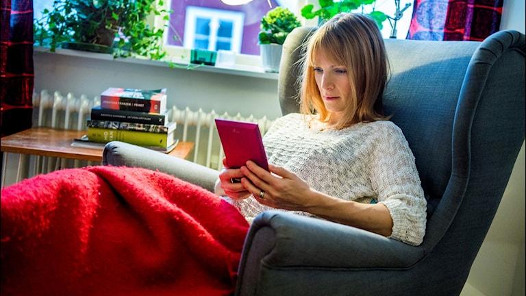 Kvinna läser bok på läsplatta.