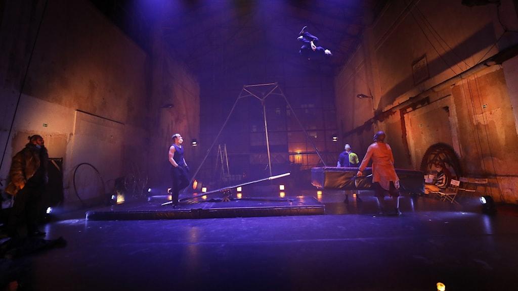 Personer gör akrobatiska konster på en scen badande i blått ljus.