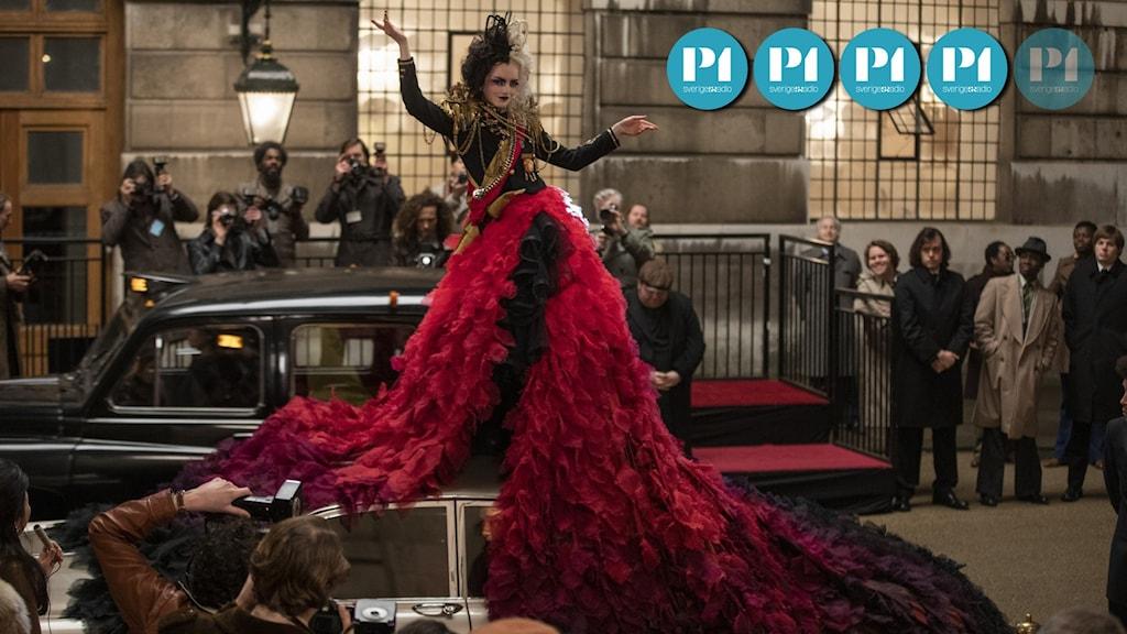 """Skådespelaren Emma Stone i filmen """"Cruella"""". Hon är klädd i röd klänning med håret i vitt och svart."""