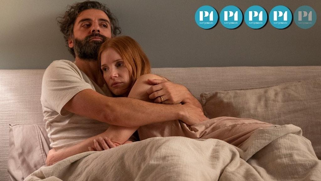 En man och en kvinna ligger i en säng och kramas med allvarliga miner.
