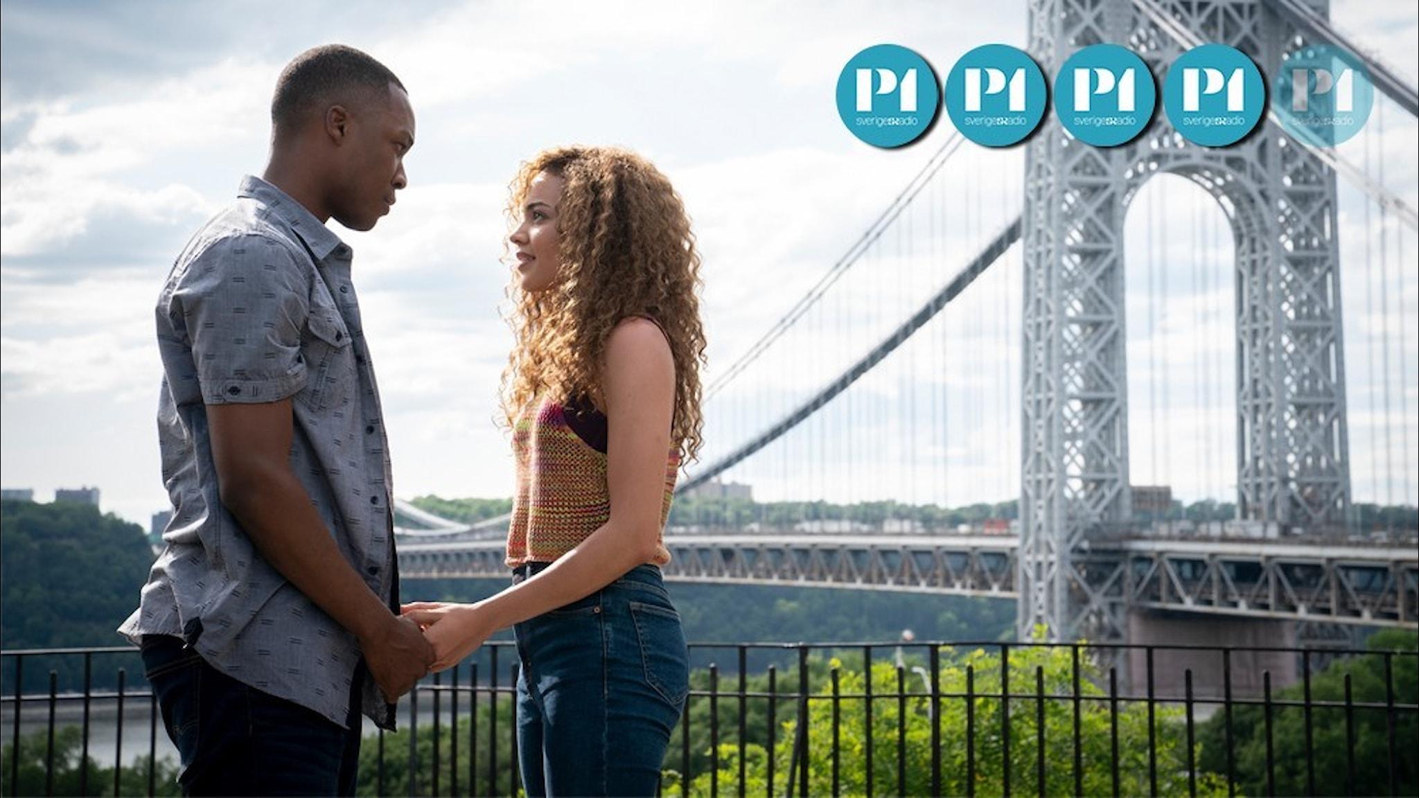 En kvinna och en man håller varandras händer och ser varandra i ögonen. Bakom dem syns en stor hängbro.