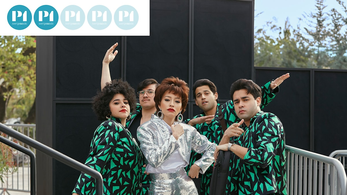 Unga människor poserar i grupp i likadana grönsvarta kläder. Sångerskan i mitten har silverkläder.