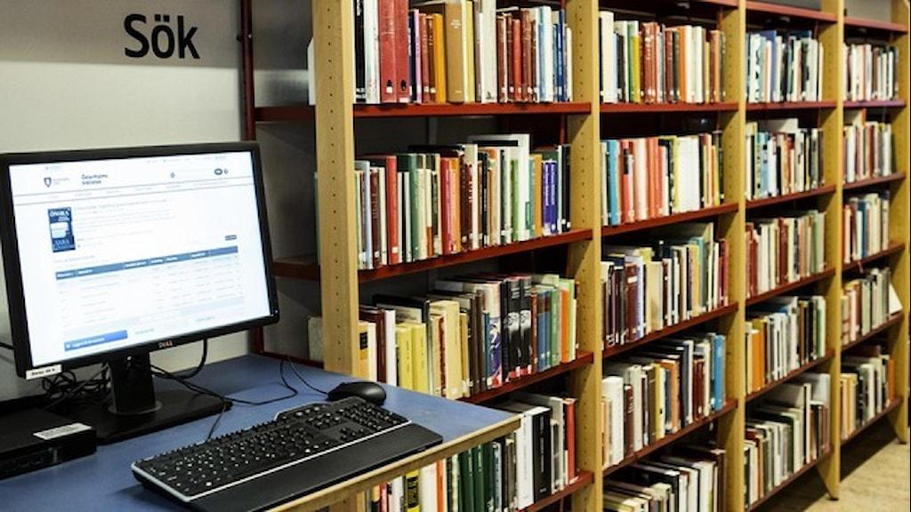 En dator och bokhyllor på ett bibliotek.