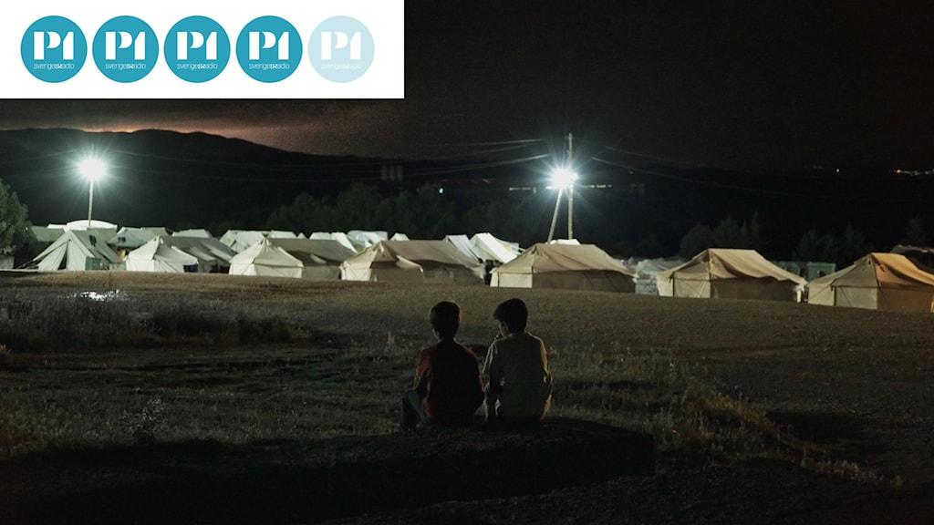 Idomeni två pojkar ses bakifrån sitta om kvällen och prata i flyktinglägret Idomeni.