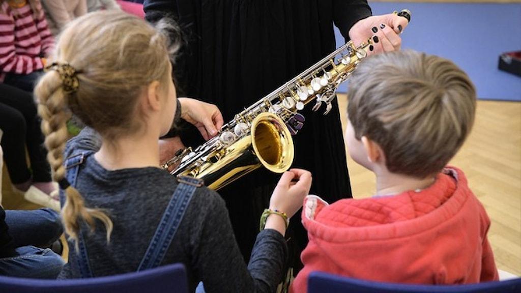 Två barn tittar på en saxofon.