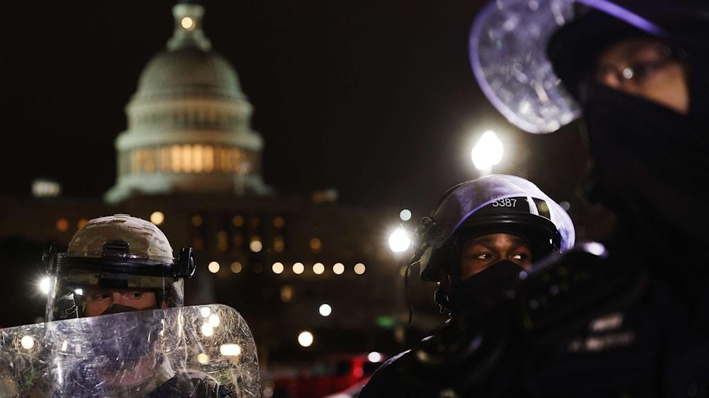 Poliser md skyddsutrustning framför Kapitolium.