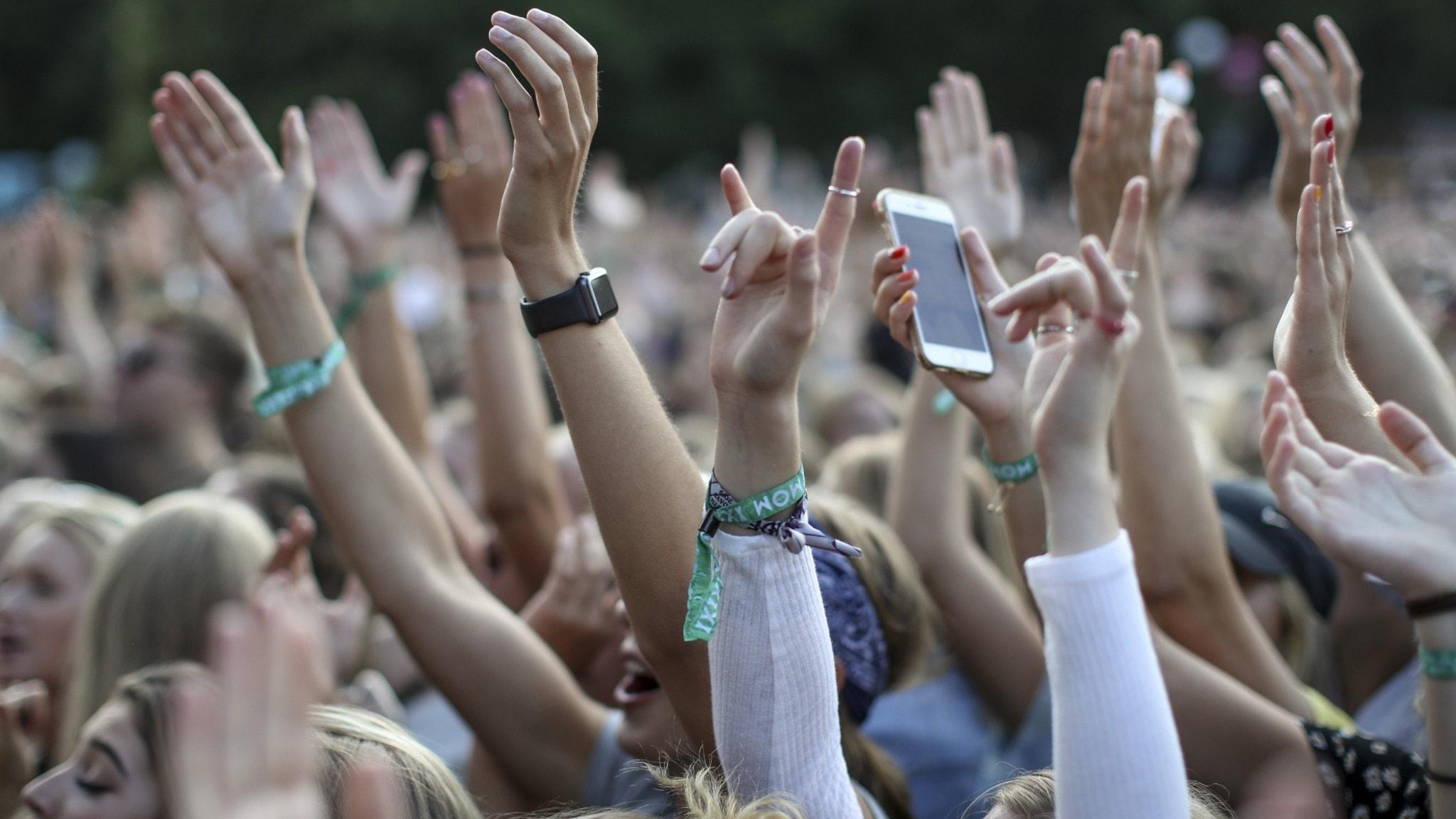 Händer i luften vid en festivalkonsert.
