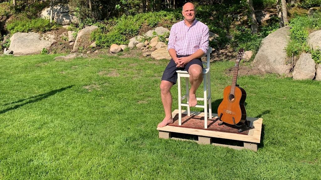 Man sittande vid gitarr på gräsmatta.