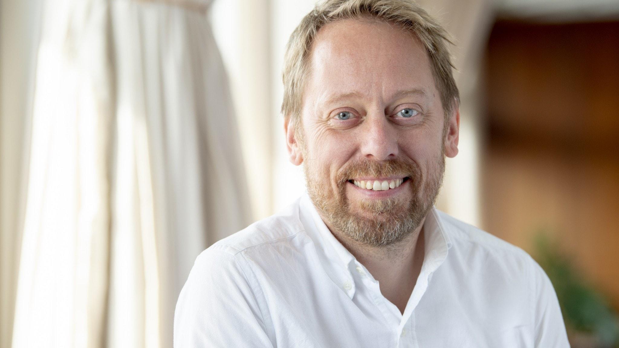 Programledaren Peter Settman klädd i vit skjorta.