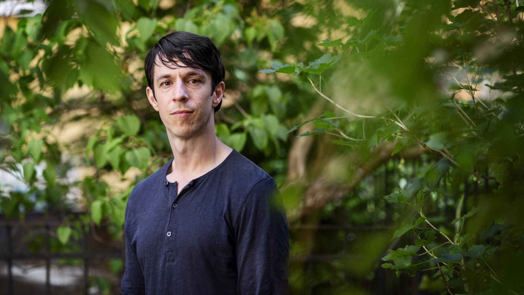 Roland Paulsen iklädd långärmad tröja framför grönska.