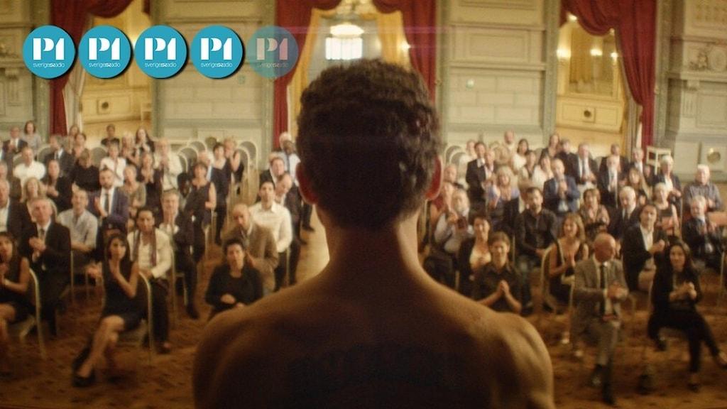 """Stillbild ur filmen """"The man who sold his skin"""": En man står med bar överkropp framför en grupp människor."""