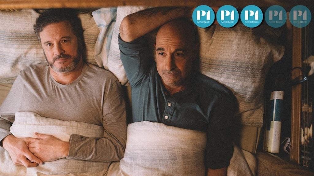 Två män ligger i en säng och tittar upp i taket.